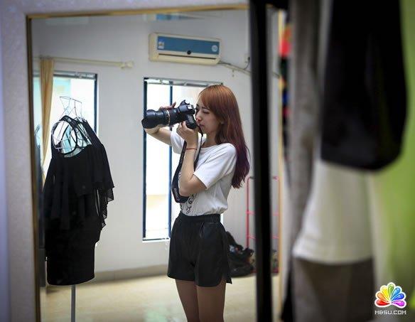 淘宝店主汪杭萍正在给衣服拍摄细节图